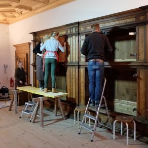 Montage des restaurierten Schrankes im Rittersaal